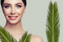 Νέα χαμογελώντας γυναίκα με το καθαρό φρέσκο δέρμα και τα πράσινα φύλλα στοκ φωτογραφία