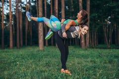 Νέα χαμογελώντας γυναίκα που ανυψώνει το φίλο της σε την πλάτη που έχει τη διασκέδαση εκπαιδευτική στο δάσος Στοκ Εικόνα