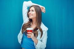 Νέα χαμογελώντας γυναίκα που κρατά το κόκκινο φλυτζάνι καφέ Στοκ φωτογραφία με δικαίωμα ελεύθερης χρήσης