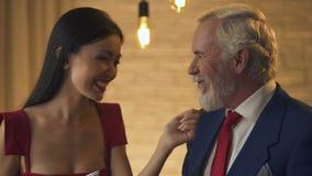 Νέα χαμογελώντας γυναίκα που φλερτάρει με τον ηληκιωμένο κατά τη ρομαντική ημερομηνία, που ταΐζει τον, αγάπη φιλμ μικρού μήκους