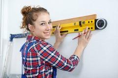 Νέα χαμογελώντας γυναίκα που χρησιμοποιεί το επίπεδο πνευμάτων στοκ φωτογραφίες με δικαίωμα ελεύθερης χρήσης