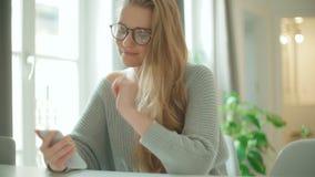 Νέα χαμογελώντας γυναίκα που χρησιμοποιεί το τηλέφωνο στο σπίτι απόθεμα βίντεο