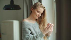 Νέα χαμογελώντας γυναίκα που χρησιμοποιεί το τηλέφωνο στο σπίτι φιλμ μικρού μήκους