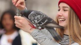 Νέα χαμογελώντας γυναίκα στα κόκκινα ταΐζοντας περιστέρια καπέλων στην οδό απόθεμα βίντεο