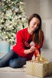 Νέα χαμογελώντας γυναίκα στο πουλόβερ που κρατά τις διακοπές ενός δώρων κιβωτίων εορτασμού χειμώνα στο διακοσμημένο εγχώριο εσωτε Στοκ εικόνες με δικαίωμα ελεύθερης χρήσης