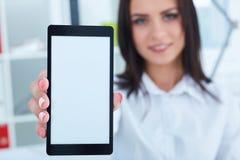 Νέα χαμογελώντας επιχειρηματίας που παρουσιάζει κενή οθόνη smartphone Εστίαση στο smartphone Στοκ Φωτογραφία