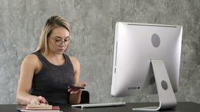 Νέα χαμογελώντας επιχειρησιακή γυναίκα που χρησιμοποιεί το smartphone κοντά στον υπολογιστή στην αρχή απόθεμα βίντεο