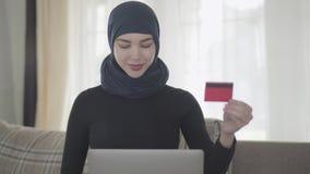 Νέα χαμογελώντας μουσουλμανική γυναίκα πορτρέτου που χρησιμοποιεί μια πιστωτική κάρτα για να πληρώσει το σε απευθείας σύνδεση χρη απόθεμα βίντεο