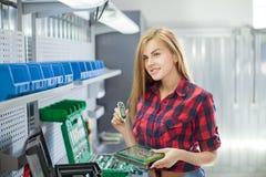 Νέα χαμογελασμένη προκλητική γυναίκα με το ηλεκτρονικό πιάτο σε ένα γκαράζ Στοκ Εικόνες
