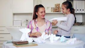 Νέα χαμογελώντας γυναίκα και κορίτσι που κατασκευάζουν τα αεροπλάνα του εγγράφου στο σπίτι φιλμ μικρού μήκους