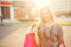 Νέα χαμογελώντας γυναίκα με τις τσάντες αγορών στην οδό Στοκ Φωτογραφία