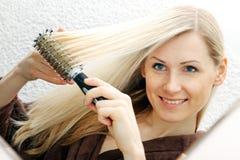 Νέα χαμογελώντας γυναίκα που βουρτσίζει τα μακριά ξανθά μαλλιά της Στοκ Εικόνα