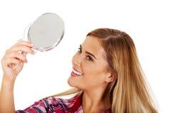 Νέα χαμογελώντας γυναίκα που κρατά έναν καθρέφτη Στοκ Εικόνες