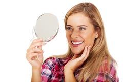 Νέα χαμογελώντας γυναίκα που κρατά έναν καθρέφτη Στοκ Φωτογραφίες