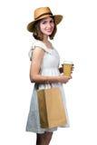 Νέα χαμογελώντας γυναίκα που κρατά μια τσάντα αγορών και ένα φλυτζάνι εγγράφου Στοκ Φωτογραφίες