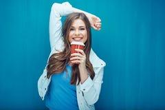 Νέα χαμογελώντας γυναίκα που κρατά το κόκκινο φλυτζάνι καφέ Στοκ Φωτογραφία