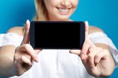 Νέα χαμογελώντας γυναίκα που παρουσιάζει οθόνη του τηλεφώνου στο μπλε υπόβαθρο διάστημα αντιγράφων Στοκ εικόνες με δικαίωμα ελεύθερης χρήσης