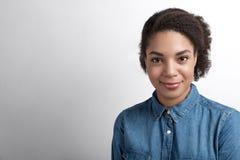 Νέα χαμογελώντας γυναίκα που φορά τα ενδύματα τζιν Στοκ Φωτογραφίες