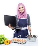 Νέα χαμογελώντας γυναίκα που φορά hijab στο PC lap-top που μαγειρεύει κάνοντας τα FO στοκ φωτογραφία