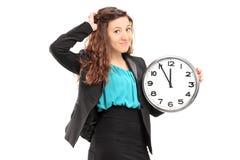 Νέα χαμογελώντας επιχειρηματίας που κρατά ένα ρολόι τοίχων Στοκ Φωτογραφίες