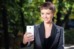 Νέα χαμογελώντας επιχειρηματίας που παίρνει τη φωτογραφία με το τηλέφωνό της υπαίθριος Στοκ Φωτογραφίες