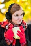 Νέα χαριτωμένα γυναίκα/κορίτσι που πίνει το καυτό τσάι σοκολάτας/κακάου στο τ Στοκ Εικόνες