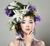 Νέα χαριτωμένη ασιατική πρότυπη γυναίκα με το λουλούδι Hairstyle ανθών στοκ εικόνες