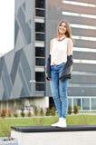 Νέα χαριτωμένη αστική γυναίκα ύφους που στέκεται στον πάγκο Στοκ εικόνα με δικαίωμα ελεύθερης χρήσης
