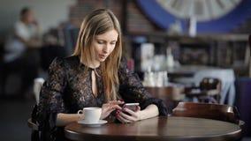 Νέα χαριτωμένη γυναίκα που χρησιμοποιεί το τηλέφωνο, που κάθεται σε έναν καφέ που κρατά ένα smartphone, που απαντά στα κείμενα Όμ απόθεμα βίντεο