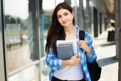 Νέα χαριτωμένη χαμογελώντας γυναίκα με το σακίδιο πλάτης και σημειωματάρια που στέκονται το ΝΕ Στοκ Φωτογραφίες