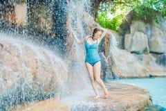 Νέα χαλάρωση γυναικών κάτω από έναν καταρράκτη στο aquapark Στοκ εικόνες με δικαίωμα ελεύθερης χρήσης