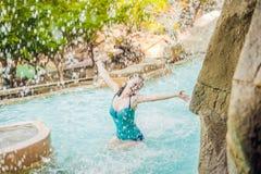 Νέα χαλάρωση γυναικών κάτω από έναν καταρράκτη στο aquapark Στοκ φωτογραφία με δικαίωμα ελεύθερης χρήσης