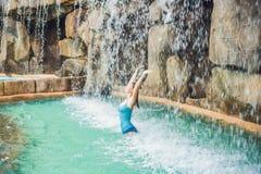 Νέα χαλάρωση γυναικών κάτω από έναν καταρράκτη στο aquapark Στοκ Φωτογραφίες