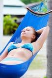 Νέα χαλάρωση γυναικών σε μια αιώρα στοκ εικόνα με δικαίωμα ελεύθερης χρήσης