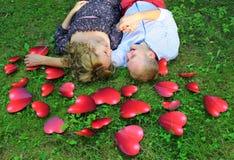 Νέα χαλάρωση ζευγών αγάπης στη χλόη μεταξύ των κόκκινων καρδιών Στοκ Φωτογραφία