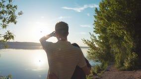 Νέα χαλάρωση ζευγών σε μια παραλία στο ηλιοβασίλεμα απόθεμα βίντεο