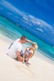 Νέα χαλάρωση ζευγών στην τροπική παραλία άμμου στο μπλε ουρανό Στοκ εικόνα με δικαίωμα ελεύθερης χρήσης