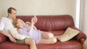 Νέα χαλάρωση ζευγών στον καναπέ στο καθιστικό, ήπια να αγκαλιάσει και να μιλήσει φιλμ μικρού μήκους