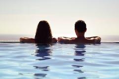 Νέα χαλάρωση ζεύγους μαζί σε μια πισίνα απείρου και απολαμβάνοντας τη θέα του ορίζοντα και της θάλασσας Διακοπές ταξιδιού και καλ Στοκ Εικόνα