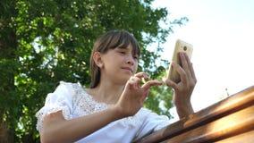Νέα χιλιετής γυναίκα στο δενδρολογικό κήπο, που κάνει τις χειρονομίες στην τηλεφωνική επίδειξη Ένα νέο κορίτσι που χρησιμοποιεί έ απόθεμα βίντεο