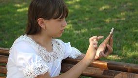 Νέα χιλιετής γυναίκα στο δενδρολογικό κήπο, που κάνει τις χειρονομίες στην τηλεφωνική επίδειξη Ένα νέο κορίτσι που χρησιμοποιεί έ φιλμ μικρού μήκους