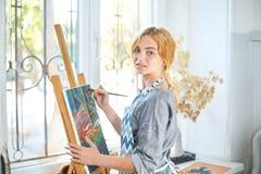 Νέα χρώματα κοριτσιών χαμόγελου στον καμβά με τα ελαιοχρώματα στο εργαστήριο παράθυρο στο υπόβαθρο τέχνης ανασκόπησης μαύρο έννοι Στοκ φωτογραφίες με δικαίωμα ελεύθερης χρήσης