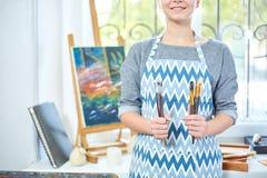Νέα χρώματα κοριτσιών χαμόγελου στον καμβά με τα ελαιοχρώματα στο εργαστήριο παράθυρο στο υπόβαθρο τέχνης ανασκόπησης μαύρο έννοι Στοκ εικόνα με δικαίωμα ελεύθερης χρήσης