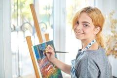 Νέα χρώματα κοριτσιών χαμόγελου στον καμβά με τα ελαιοχρώματα στο εργαστήριο παράθυρο στο υπόβαθρο τέχνης ανασκόπησης μαύρο έννοι Στοκ Φωτογραφία