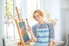 Νέα χρώματα κοριτσιών χαμόγελου στον καμβά με τα ελαιοχρώματα στο εργαστήριο παράθυρο στο υπόβαθρο τέχνης ανασκόπησης μαύρο έννοι Στοκ Εικόνες