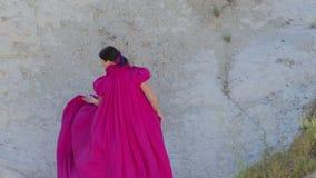 Νέα ψηλά πρότυπα τρεξίματα κοριτσιών σε ένα μακρύ πορφυρό φόρεμα με μια ουρά στα βουνά απόθεμα βίντεο