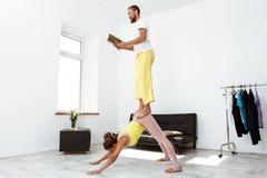 Νέα όμορφα αθλητικά asanas γιόγκας συνεργατών κατάρτισης ζευγών στο σπίτι Στοκ εικόνες με δικαίωμα ελεύθερης χρήσης