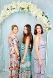 Νέα όμορφα κορίτσια στα φωτεινά χρωματισμένα φορέματα 9 πολύχρωμες εικόνες διάθεσης που τίθενται τις τουλίπες άνοιξη θαυμάσιες Στοκ Φωτογραφίες