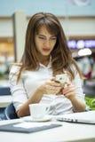 Νέα όμορφα μηνύματα ανάγνωσης επιχειρησιακών γυναικών στοκ εικόνα