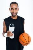 Νέα όμορφα σφαίρα και μπουκάλι νερό καλαθιών εκμετάλλευσης αθλητικών τύπων Στοκ φωτογραφία με δικαίωμα ελεύθερης χρήσης